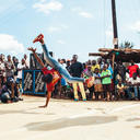 A young Ugandan break dances in front of a crowd