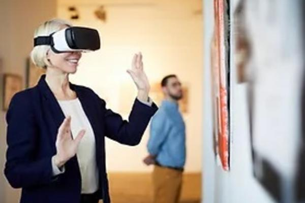 A woman wears a virtual reality headset and stands opposite a painting.