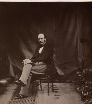 Prince Albert sits in a chair looking at the camera in a Victorian photograph.